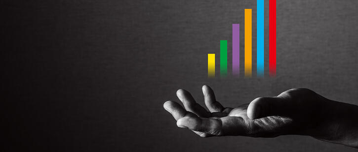 Hand holding a colourful bar graph